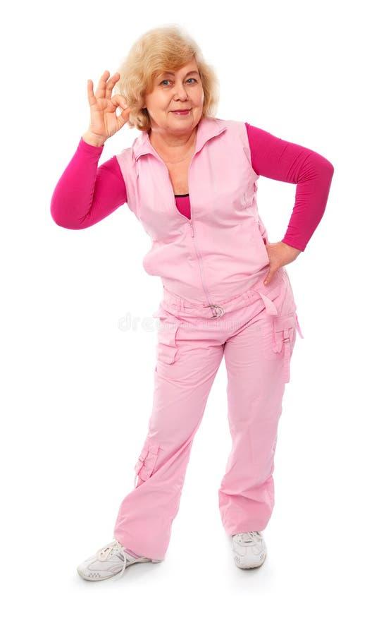A posição idosa feliz ativa da mulher mostra ESTÁ BEM imagens de stock royalty free