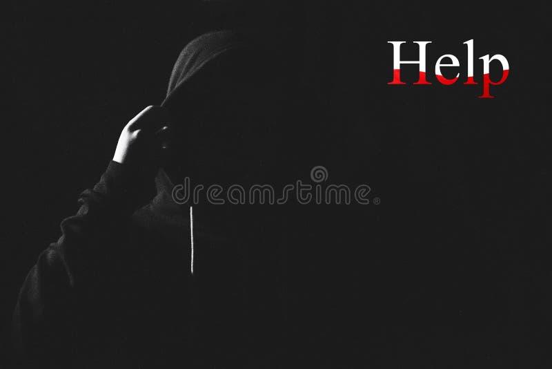Posição irritada do homem em uma capa na obscuridade foto de stock