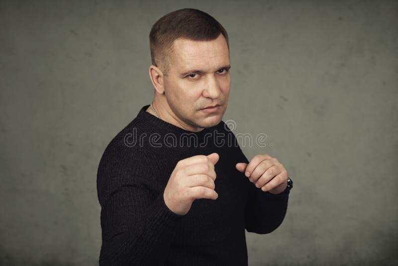 Posição irritada do homem em uma posição de combate fotos de stock