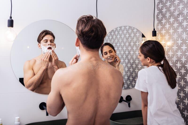 Posição justa do casal no banheiro que olha em espelhos imagem de stock