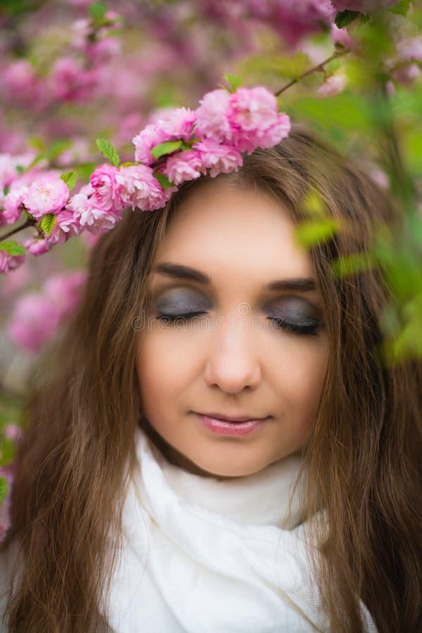 A posição loura bonita da menina em um lenço branco e fechou seus olhos no jardim das flores de cerejeira foto de stock