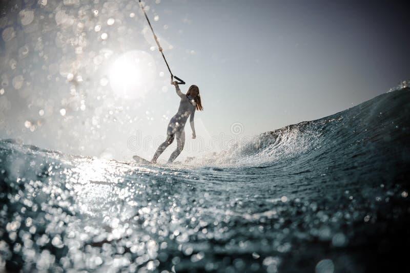 Posição loura da menina no wakeboard que guarda uma corda imagens de stock royalty free
