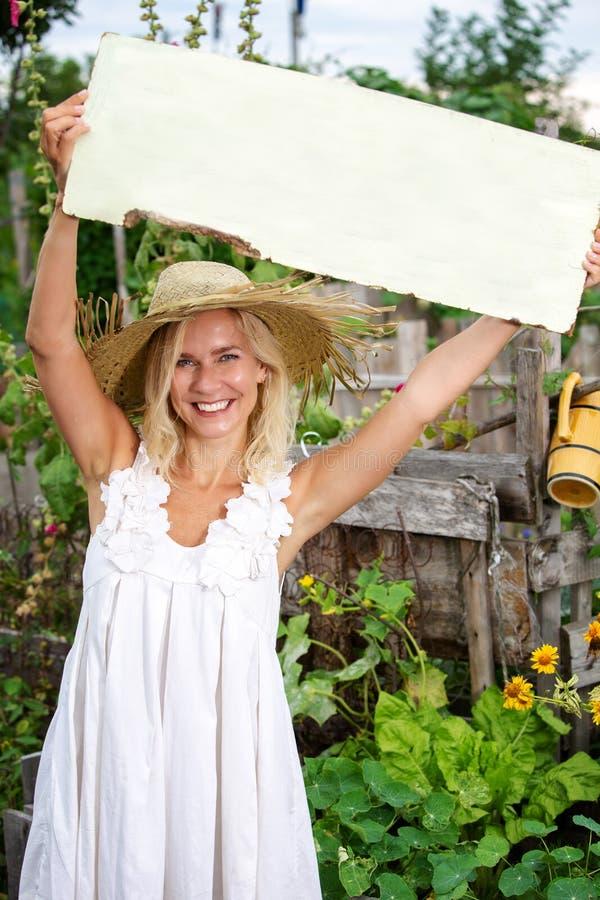 Posição loura da mulher no jardim e guardar um sinal de madeira fotos de stock royalty free
