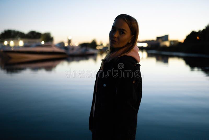 Posição loura do retrato da mulher pelo rio na noite foto de stock