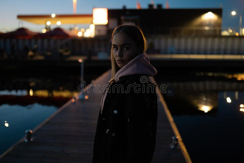 Posição loura do retrato da mulher pelo rio na noite imagens de stock