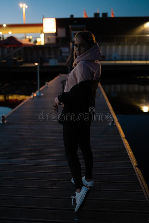 Posição loura do retrato da mulher pelo rio na noite imagens de stock royalty free