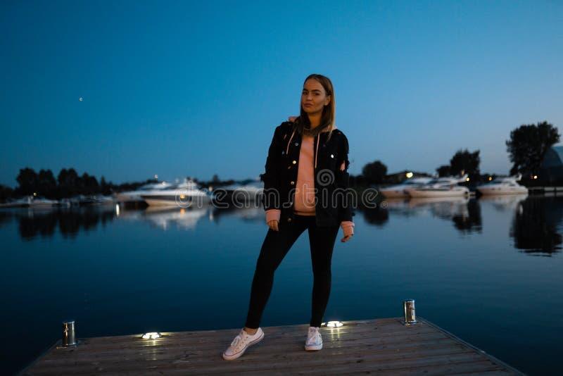 Posição loura do retrato da mulher pelo rio na noite fotos de stock