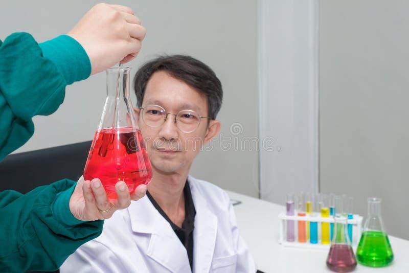 Posição masculina do cientista com techer no técnico de laboratório que faz a investigação médica no cientista moderno do laborat fotografia de stock royalty free