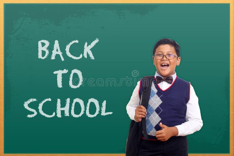 A posição masculina do estudante da escola primária na classe ao vestir o uniforme e leva o saco com garatujas, comemora de volta fotos de stock