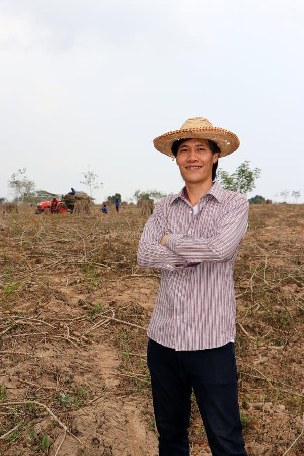 Posição masculina do fazendeiro e caixa do aperto na exploração agrícola da mandioca imagens de stock