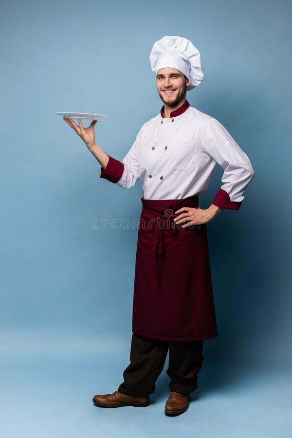 Posição masculina feliz do cozinheiro do cozinheiro chefe com a placa isolada em claro - fundo azul imagem de stock