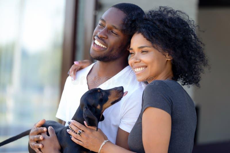Posição milenar africana feliz dos pares que guarda fora o cachorrinho do bassê imagens de stock royalty free