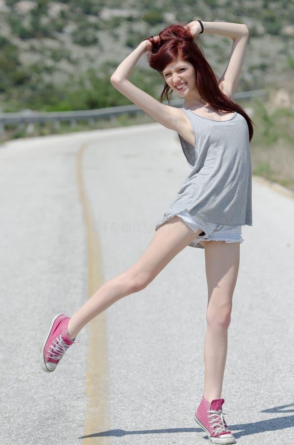 Posição modelo atrativa no meio de uma estrada da montanha fotos de stock