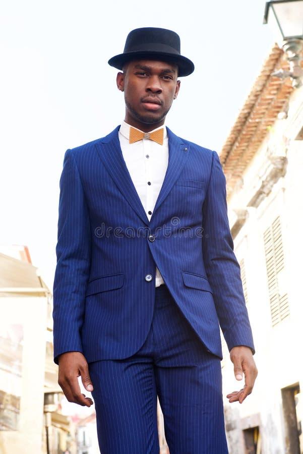 Posição modelo masculina afro-americano fresca na rua da cidade com terno e bowtie fotografia de stock