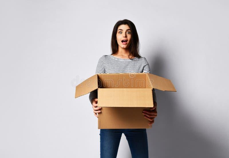 Posição moreno bonita da mulher em um fundo claro com uma caixa de cartão movente fotografia de stock