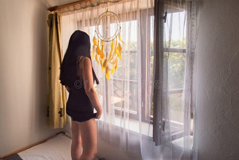 Posição moreno da mulher e vista fora da janela - vista lateral fotografia de stock