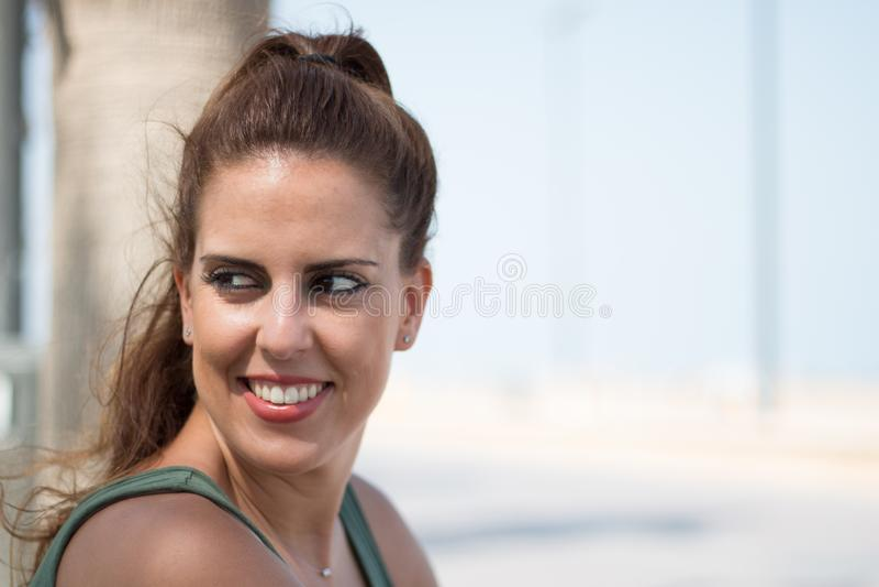 Posição moreno do retrato do lado da mulher exterior, olhando à esquerda, com fundo unfocused imagens de stock royalty free