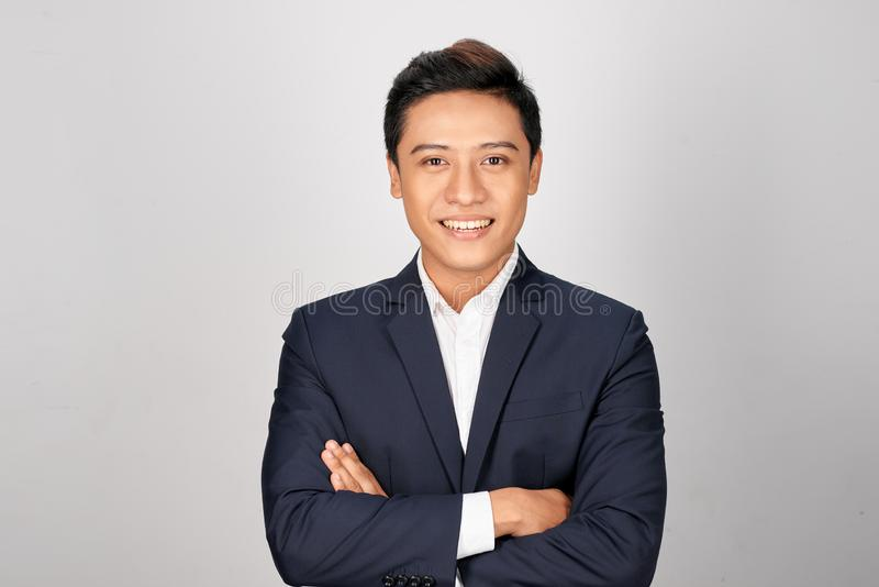 Posição nova asiática feliz do homem de negócios cruz-armada no fundo branco fotografia de stock