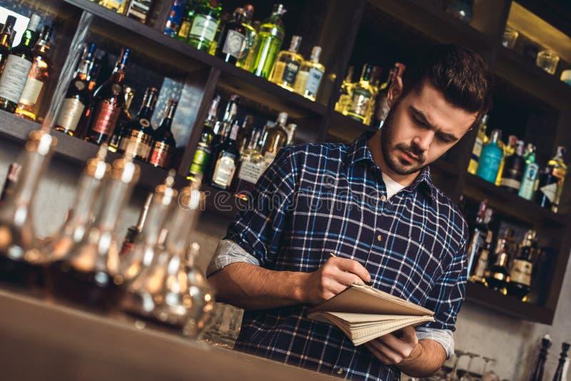 Posição nova do barman na receita da escrita do contador da barra no caderno pensativo imagem de stock