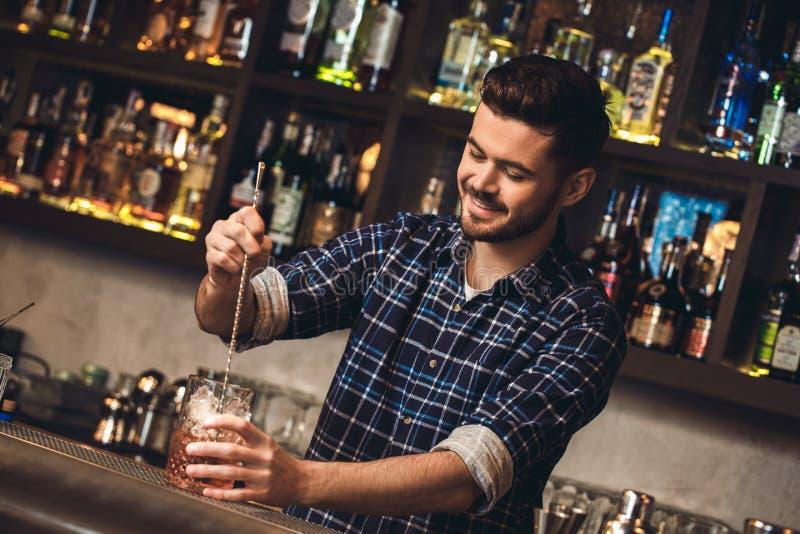 Posição nova do barman no cocktail de mistura do contador da barra com a colher da barra alegre imagens de stock