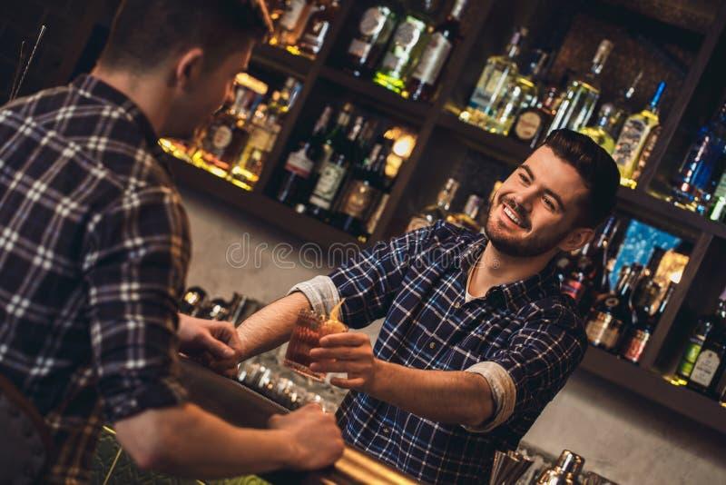 Posição nova do barman no contador da barra que dá o cocktail do cliente alegre fotografia de stock