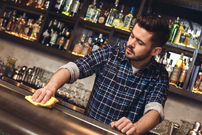 Posição nova do barman no contador da barra que limpa a superfície concentrada imagem de stock