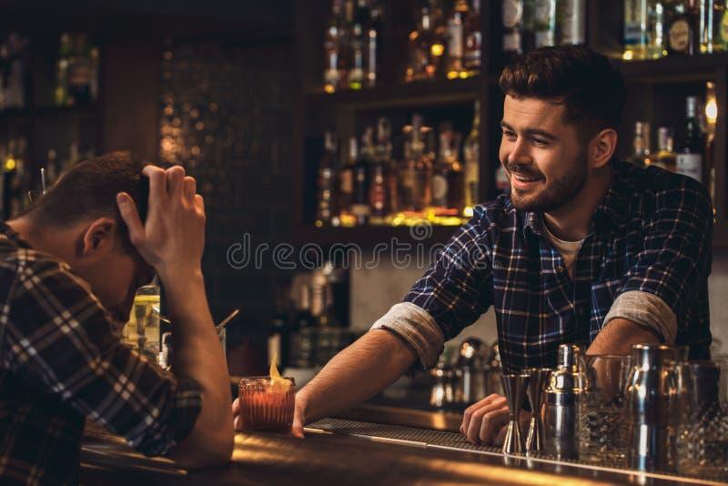 Posição nova do barman no contador da barra que serve o cliente que cheering acima imagem de stock