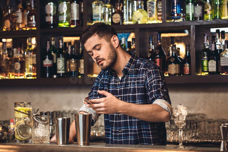 Posição nova do barman no ingrediente de derramamento do contador da barra no abanador concentrado imagem de stock
