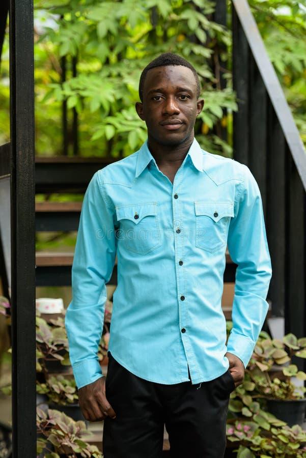 Posição nova do homem do africano negro contra a escadaria moderna com n foto de stock