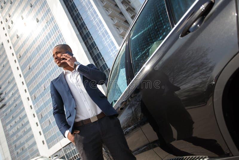 Posição nova do homem de negócios perto do carro que fala na opinião inferior pensativa do smartphone imagem de stock