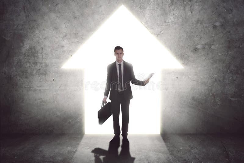 Posição nova do homem de negócios perto de uma porta brilhante fotografia de stock royalty free