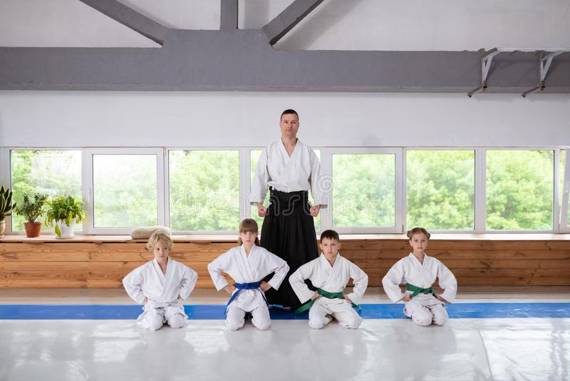 Posição nova do instrutor do aikido perto de seus alunos pequenos imagem de stock royalty free
