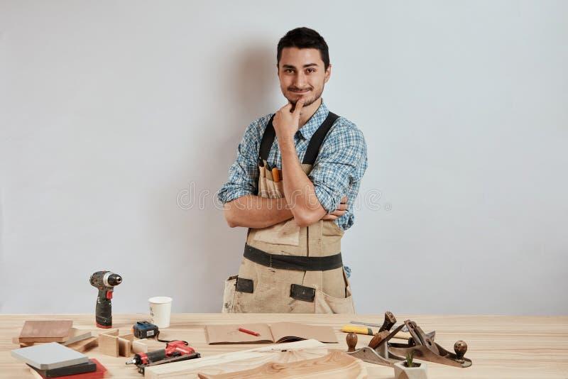 Posição nova segura do carpinteiro ao lado da bancada em sua oficina da carpintaria fotografia de stock royalty free