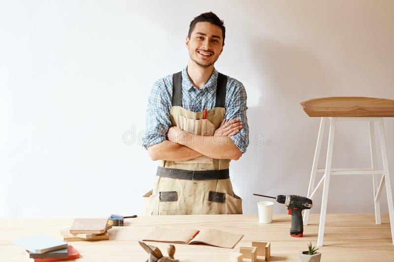 Posição nova segura do carpinteiro ao lado da bancada em sua oficina da carpintaria foto de stock