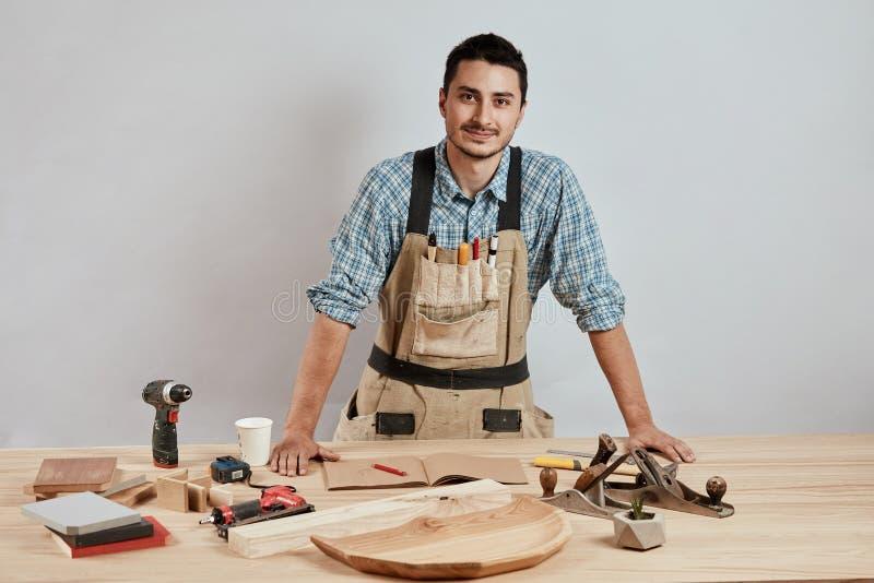 Posição nova segura do carpinteiro ao lado da bancada em sua oficina da carpintaria imagens de stock royalty free