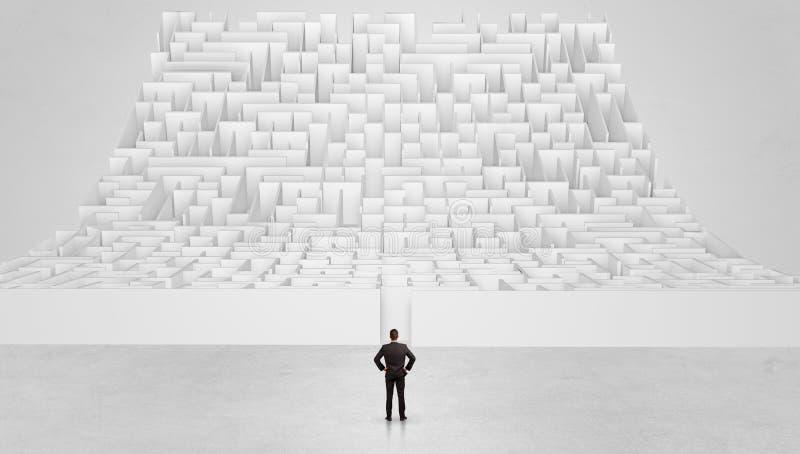 Posição pequena do homem na frente de um labirinto da infinidade foto de stock