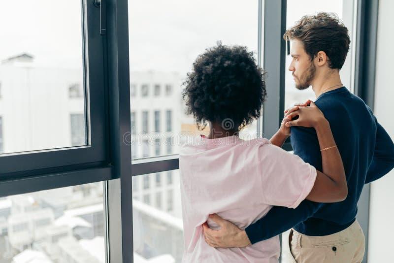 Posição romântica dos pares da raça misturada pela janela que pensa sobre seu futuro imagens de stock royalty free