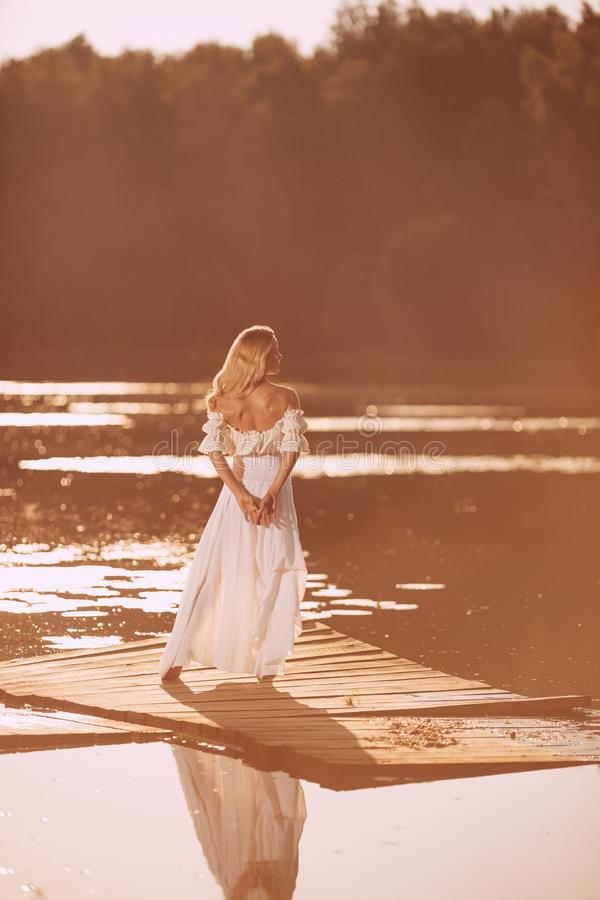 Posição sensual da jovem mulher pelo lago no por do sol ou no nascer do sol imagem de stock