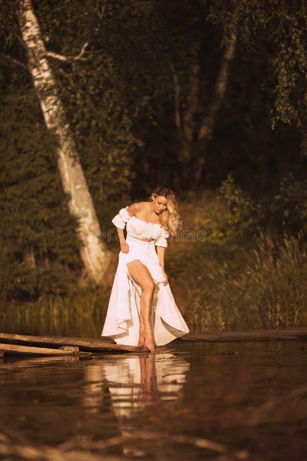 Posição sensual da jovem mulher pelo lago que mostra seus pés 'sexy' fotos de stock royalty free