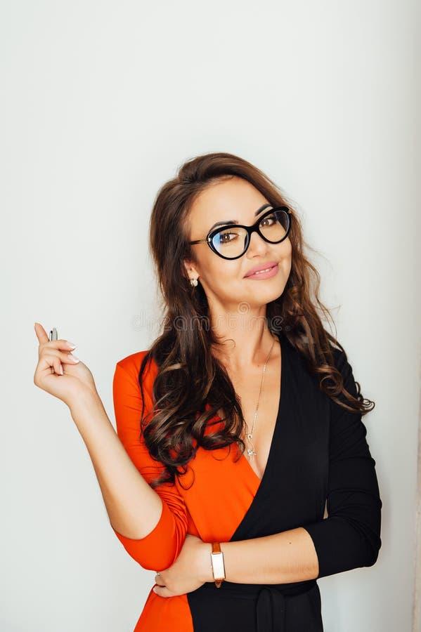 Posição 'sexy' mesma da mulher de negócio na parede branca em seu escritório imagem de stock