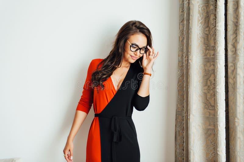 Posição 'sexy' mesma da mulher de negócio na parede branca em seu escritório fotografia de stock royalty free