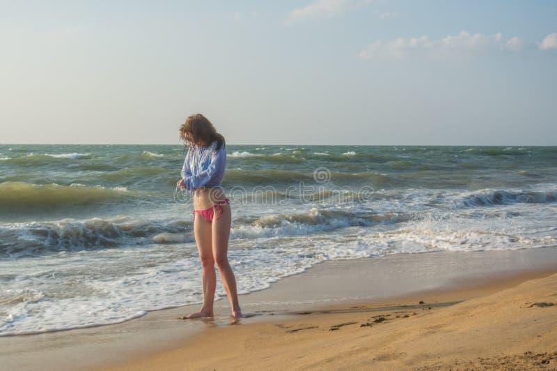Posição 'sexy' nova bonita da mulher na praia imagens de stock