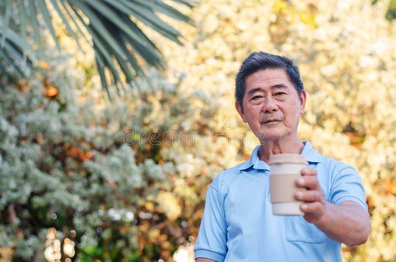 A posição superior asiática do cavalheiro no parque e guardar da mão levam embora o copo de café em um dia ensolarado imagens de stock royalty free