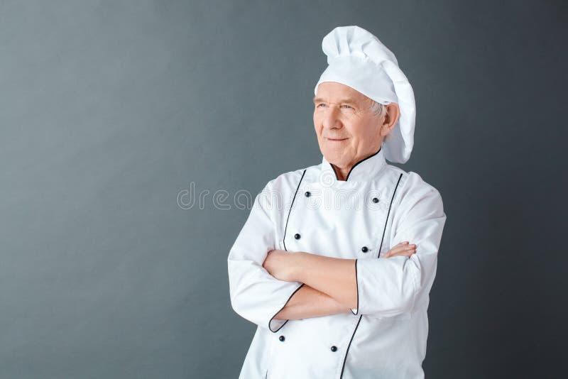Posição superior do estúdio do cozinheiro chefe isolada nos braços cruzados cinzentos que olham de lado pensativos foto de stock royalty free