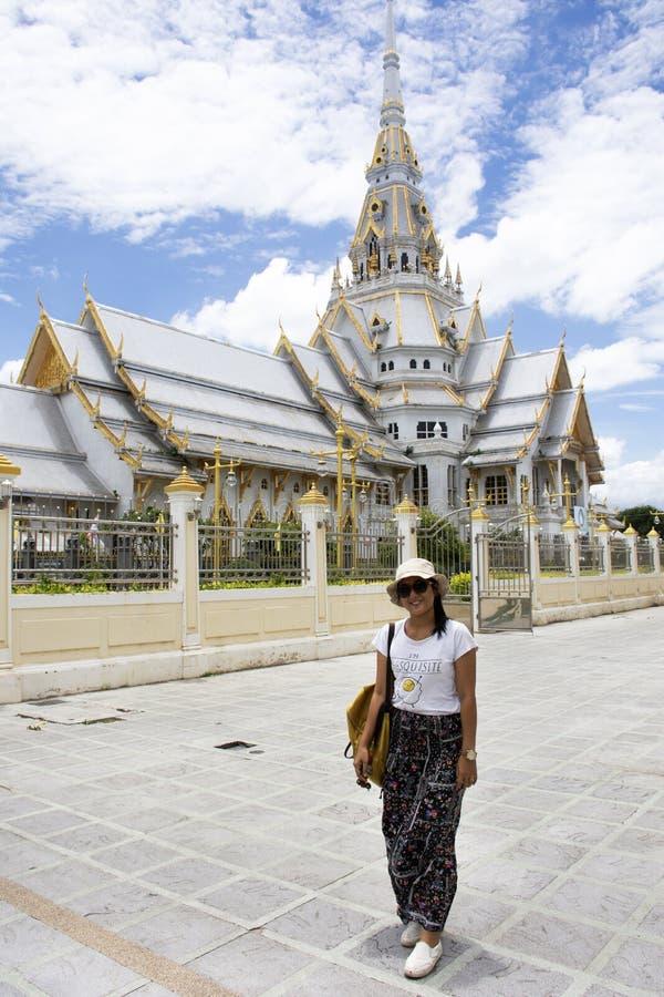 Posição tailandesa da mulher que levanta para a foto da tomada com o Ubosot de Wat Sothon Wararam Worawihan em Chachoengsao, Tail imagem de stock royalty free