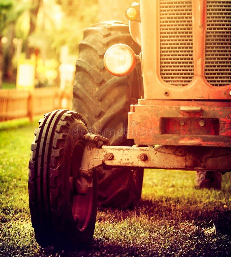 Posição vermelha do trator do vintage velho em um campo de exploração agrícola no por do sol foto de stock