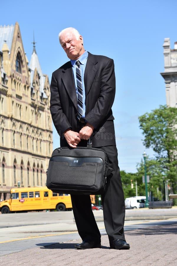 Posição vestindo do terno e do laço do acionista superior adulto infeliz do homem de negócio imagem de stock royalty free