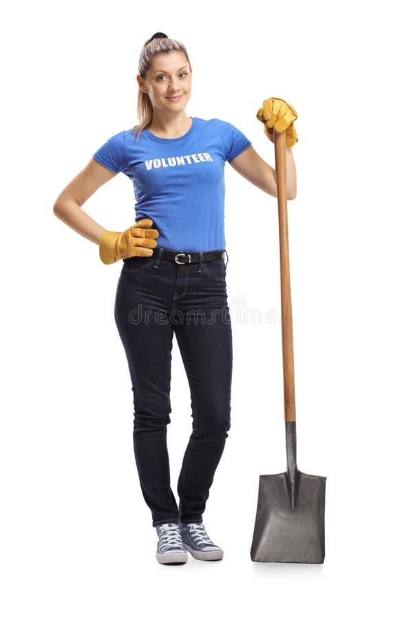 Posição voluntária da mulher com uma pá foto de stock