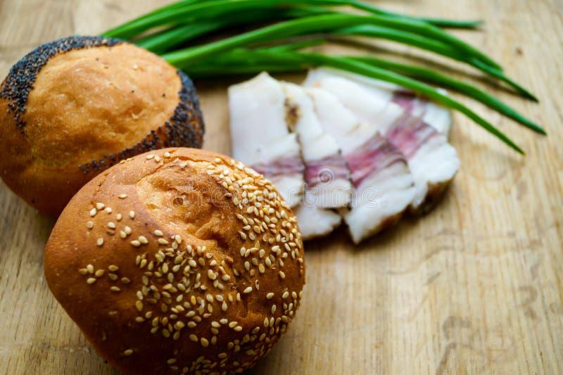 Posiłki chleb wiosen cebule i okrasa, są na drewnianym stole zdjęcia royalty free