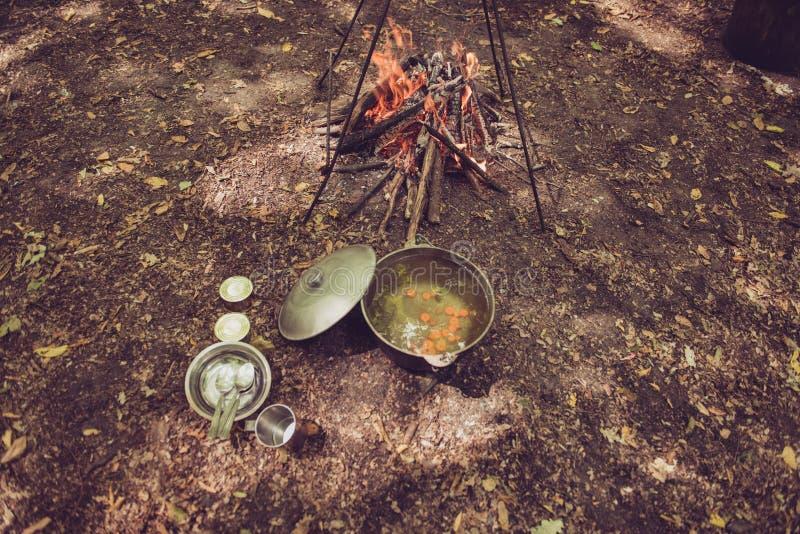 Posiłku czas Wysokiego kąta widok polewka w czajniku blisko obozu, obraz stock